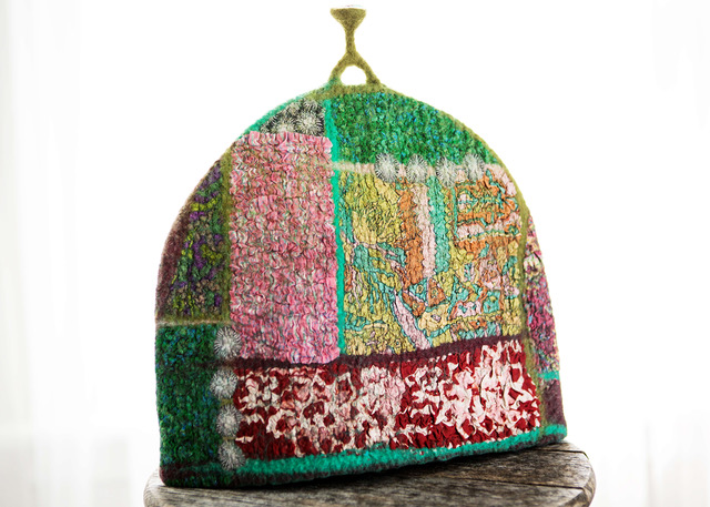 Muticoloured felt tea cosy, predominently red, pinks and greens